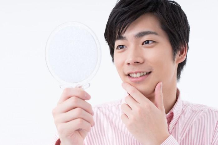 手鏡でアゴヒゲをチェックする男性
