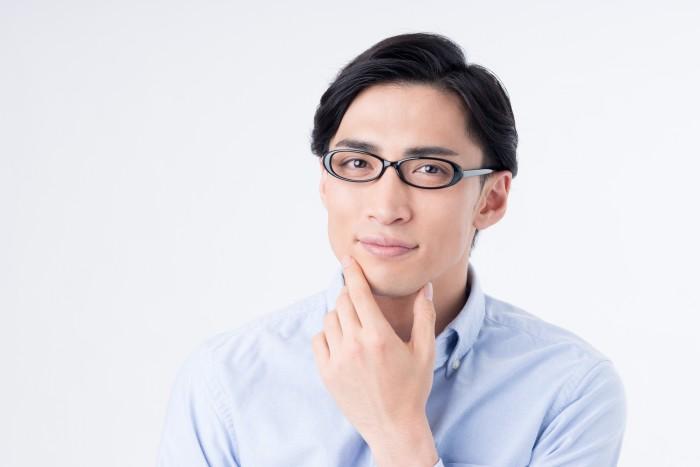 顎に左手を当てるメガネの男性