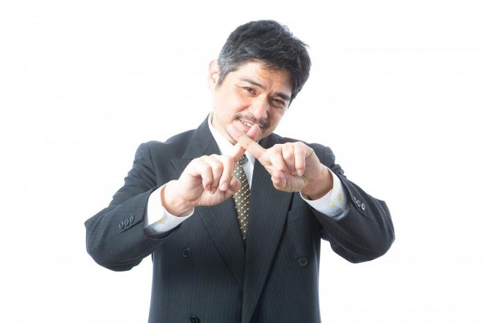 指で×印をする男性