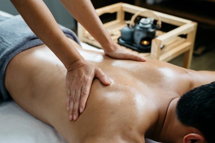 メンズエステで背中ニキビの施術を受ける男性