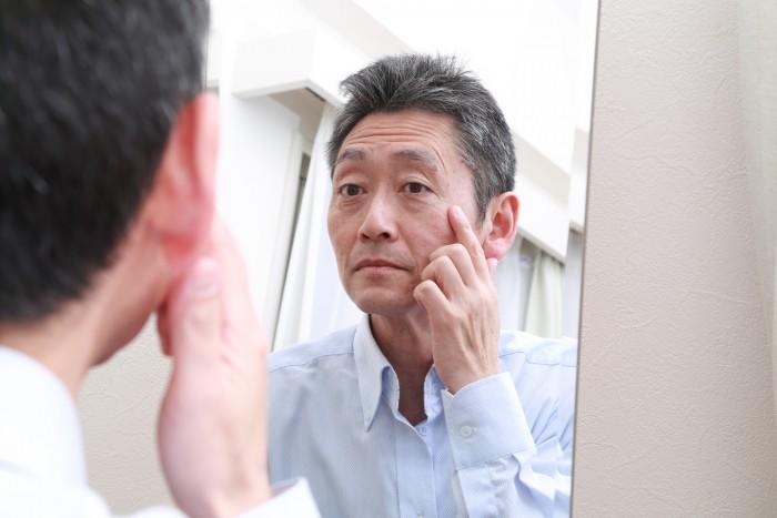 鏡を見て目元を気にする男性