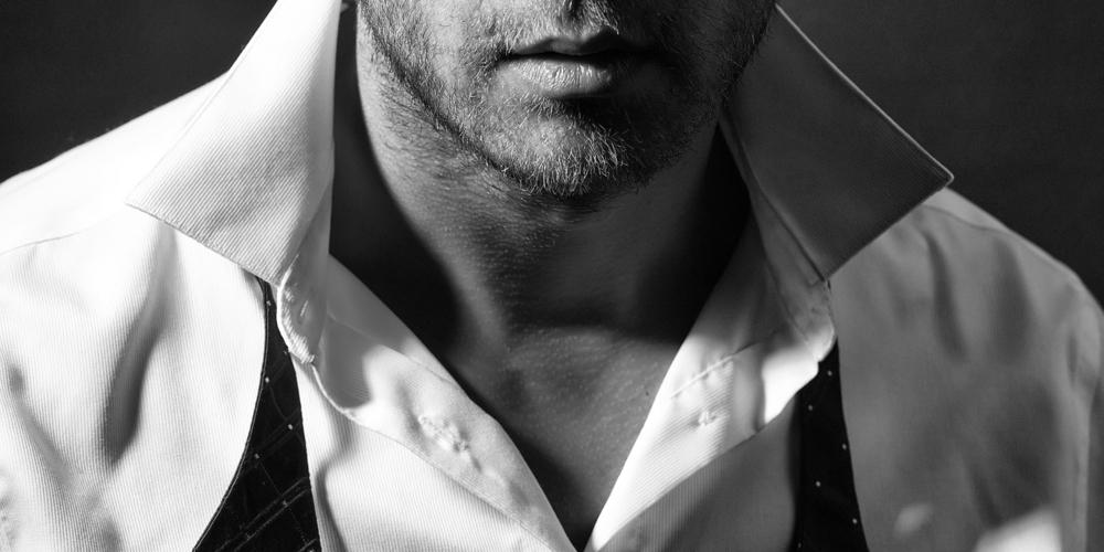 シャツの胸元が大きく開いた男性