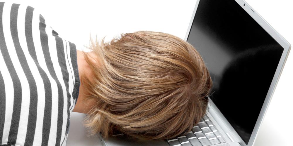 疲れてパソコンにもたれかかる男性